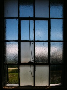 An old window with some panes frosted, some panes clear, and some panes broken.